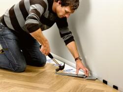 Ламинат является наиболее популярным напольным покрытием. Он способен полностью преобразить помещение, заставив его заиграть новыми красками. При этом ламинат имеет приемлемую цену, что позволяет приобретать ламинат для каждой комнаты или офиса. Разнообразие расцветок делает этот материал поистине универсальным. Ламинат можно положить на любое основание. Особое внимание необходимо уделить деревянному полу – многие сомневаются, можно ли вообще класть ламинат на такое основание. Можно, если только правильно подготовить пол. Давайте поговорим, как уложить ламинат на деревянный пол самостоятельно.  В первую очередь вы должны сделать пол, на который будет уложен ламинат, идеально ровным. Рассмотрите пол. Если он имеет достаточно большое количество неровностей и дефектов, то есть деформация превышает 3 мм на 1 м², то вам обязательно нужно приступить к выравниванию. Если же показатель деформации не превышает 3 мм, то в этом случае пол можно считать ровным и пропустить шаг по выравниванию. Шлифовка  Такой метод выравнивания деревянного пола применяется в том случае, если неровности на поверхности превышают 3 мм, но при этом меньше 5 мм на 1 м². Шлифовка выполняется специальной шлифовальной машиной. Вы можете пользоваться ей самостоятельно, а можете вызвать мастеров для проведения этой работы. Не забудьте перед началом процесса проверить пол на наличие выступающих гвоздей – их необходимо заглубить, чтобы не повредить шлифовальное устройство. Разделите пол на несколько участков, после шлифования каждого участка проверяйте качество работы и плоскость.  Использование рубанка Если на вашем полу имеются деревянные выступы и выпуклости, которые необходимо срезать, они удаляются при помощи электрорубанка. Перед работой также проверьте пол на наличие гвоздей. Если какие-то заглубить не удастся, удалите их гвоздодером. Пользоваться рубанком сможет каждый, поэтому этот процесс не требует объяснений. Использование лаг Такой метод выравнивания пола незаменим в том случае, если пол имеет